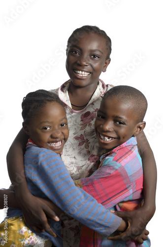 canvas print picture Drei afrikanische Kinder halten sich im Arm