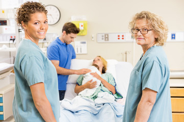 Successful Nurses Standing Against Couple With Baby In Backgroun