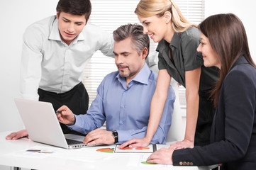 Middle aged businessman showing company strategy on laptop.