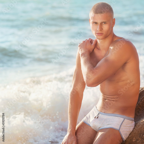Portrait of a handsome young muscular man in swimtrunks with wat