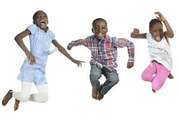Drei afrikanische Kinder springen vor Freude in die Luft
