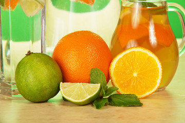Jug with drink, glass, juicy lime and oranges