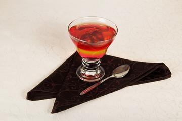 Glass of fruit jelly, teaspoon and napkin