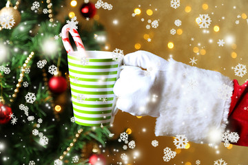 Santa holding mug in his hand, on bright background
