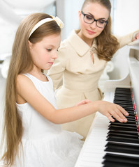 Master teaches little girl to play piano