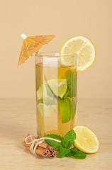 Drink glass, slice of a lemon and cinnamon stick