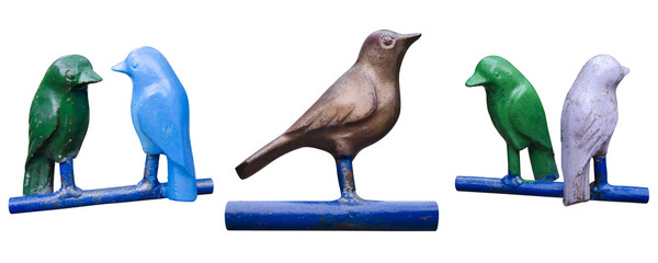 Set of isolated metal birds on perches