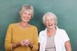 zwei seniorinnen stehen vor der schultafel