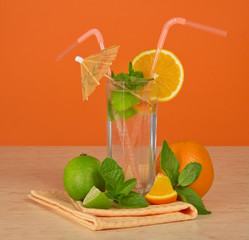 Glass with drink, ripe orange, juicy lime