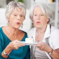 zwei ältere freundinnen blasen kerzen auf dem kuchen aus