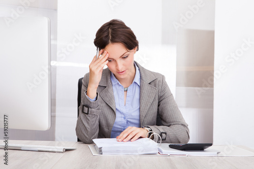 Thoughtful Businesswoman Doing Calculations