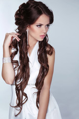 Beautiful woman with long brown hair wearing in white dress isol