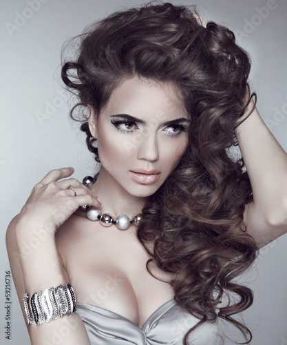 Wavy Hair. Fashion girl model with long curly hairstyle. Wellnes