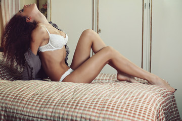 Beautiful lingerie model posing on the bed