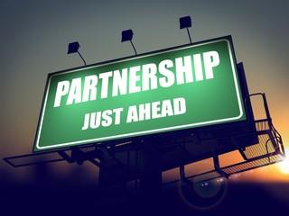 Partnership Just Ahead on Green Billboard.