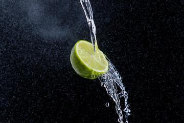 Limette auf schwarzen Grund mit Wasser