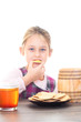 girl eating cookies with honey on a white background isolated