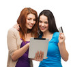 two smiling girls with tablet pc and credit card