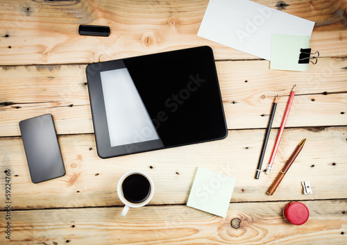 Workplace, tablet pc and smart phoned on wooden table