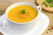 Vegetarian pumpkin soup in white bowl on wooden table