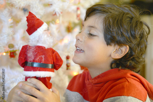 Boy holding Santa in his hands, smiling