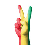 Hand making the V sign, Guinea flag painted