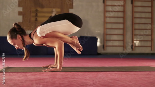 Young flexible Female doing yoga Crane pose