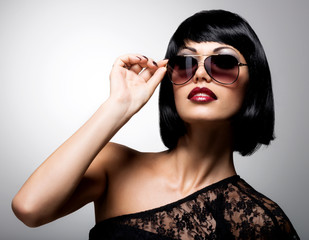 beautiful brunette woman with shot hairstyle with red sunglasses