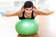 Young athletic man exercising workout fitness ball at the gym