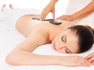 Woman having hot stone massage in spa salon.