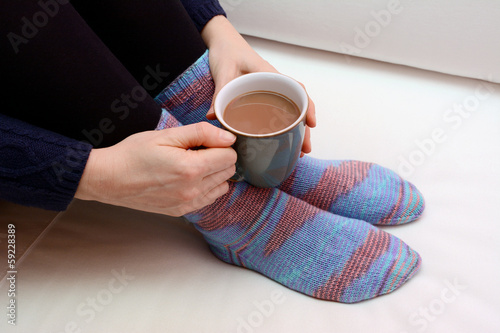 Woman holding a hot drink, wearing warm knitted socks