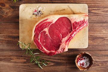raw beef Rib bone  steak   on wooden board and table