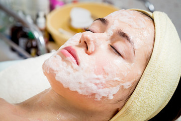 Hands of cosmetologist apply cream to face of woman.