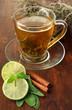 Transparent cup of green tea with lime and cinnamon