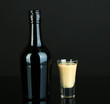 Baileys liqueur in bottle and glass isolated on black