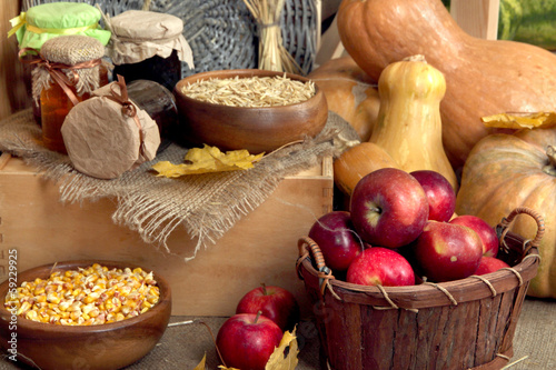 Fruits and vegetables with jars of jam and bowls of grains