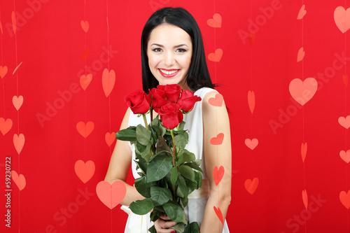 Attractive young woman with roses on Valentine Day