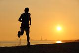 Fototapeta Backlight of a man running on the beach at sunset