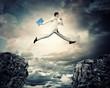 Businessman jumping over gap