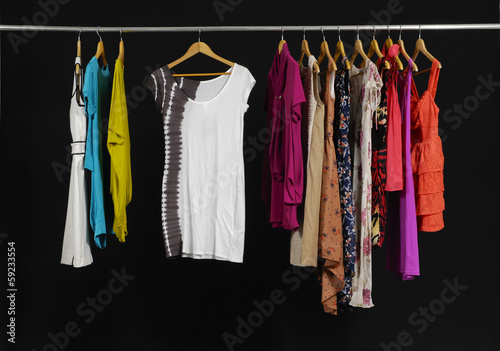 Variety of casual fashion clothing hanging on hangers on black
