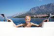 Happy girl bathes in sea near boat