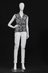 full-length mannequin female dressed in shirt and white trousers