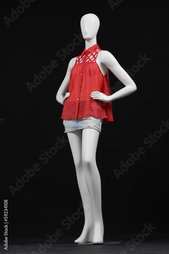 full-length female mannequin dressed in red dress and jeans