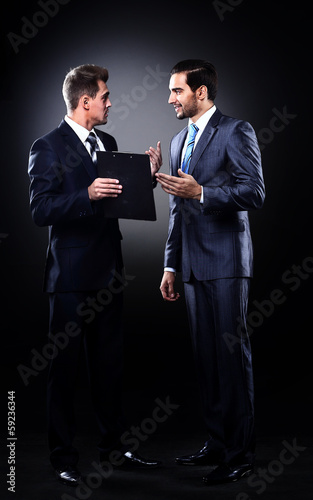 Two businessmen discussing, isolated over black background