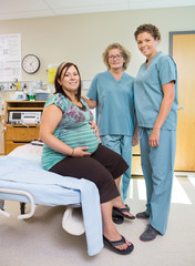 Female Nurses With Pregnant Woman In Hospital Room
