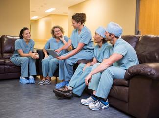 Doctor Showing Digital Tablet To Team
