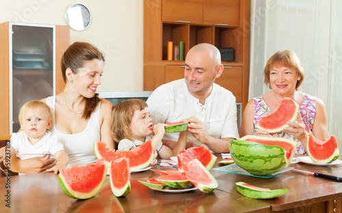 happy three generations family eating  melon