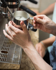 Barista Steaming Milk In Coffeeshop