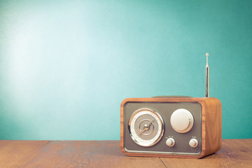 Retro style radio receiver on table front mint green background
