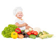 happy small kitchen boy in cook cap around variegated vegetables